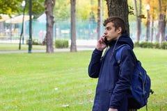Retrato del individuo de Tenager con un teléfono que habla del smartphone Parque al aire libre Fotos de archivo