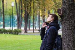 Retrato del individuo de Tenager con un teléfono que habla del smartphone Parque al aire libre Imágenes de archivo libres de regalías