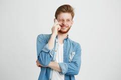 Retrato del individuo hermoso joven con el discurso sonriente de la barba en el teléfono sobre el fondo blanco Fotos de archivo
