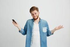 Retrato del individuo hermoso joven que sostiene el teléfono elegante que encoge mirando la cámara sobre el fondo blanco Fotografía de archivo libre de regalías