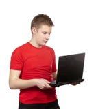Retrato del individuo joven en una camiseta roja con el ordenador portátil negro Fotografía de archivo