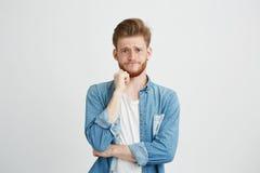 Retrato del individuo joven del trastorno triste que mira la cámara con la mano en la barbilla sobre el fondo blanco Imagenes de archivo