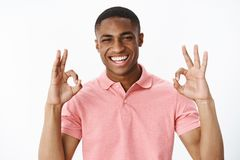Retrato del individuo positivo joven afroamericano apuesto ambicioso que muestra gesto aceptable con ambas manos y sonrisa imagen de archivo