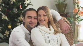 Retrato del individuo y de la muchacha alegres en el amor que se sienta cerca del árbol de navidad en casa Novio blando de la rel metrajes