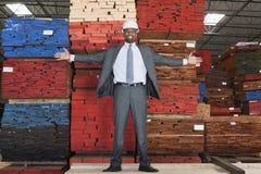 Retrato del ingeniero de sexo masculino afroamericano feliz que se coloca con los brazos extendidos delante de tablones de madera  fotos de archivo
