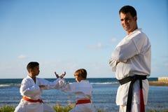 Retrato del instructor confiado Watching Children Fight del karate foto de archivo libre de regalías