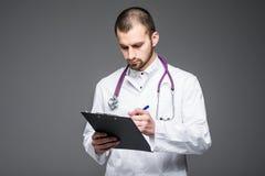 Retrato del interno sonriente barbudo del médico que sostiene el tablero con el papel vacío El doc. está llevando soportes del un fotografía de archivo libre de regalías
