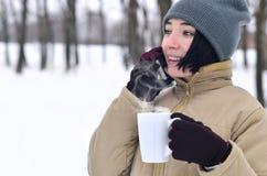 Retrato del invierno de la chica joven con la taza del smartphone y de café Imágenes de archivo libres de regalías