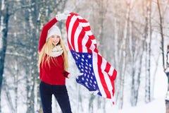 Retrato del invierno de la muchacha adolescente joven con la bandera de los E.E.U.U. Belleza Girl modelo alegre que ríe y que se  Imágenes de archivo libres de regalías