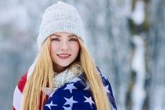 Retrato del invierno de la muchacha adolescente joven con la bandera de los E.E.U.U. Belleza Girl modelo alegre que ríe y que se  Imagen de archivo libre de regalías