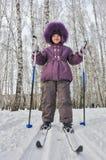 Retrato del invierno de la muchacha de cuatro años en los esquís Foto de archivo libre de regalías