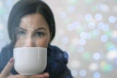 Retrato del invierno de la mujer morena joven con la taza de té que lleva la redecilla hecha punto fotos de archivo