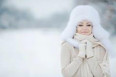 Retrato del invierno de la mujer sonriente hermosa con los copos de nieve en las pieles blancas Imagenes de archivo