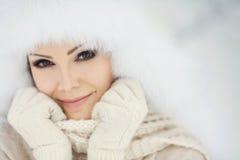 Retrato del invierno de la mujer sonriente hermosa con los copos de nieve en las pieles blancas Foto de archivo