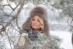 Retrato del invierno de la mujer sonriente hermosa con los copos de nieve en las pieles blancas Imágenes de archivo libres de regalías