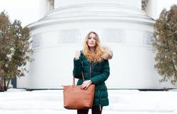 Retrato del invierno de una muchacha hermosa en una chaqueta con un bolso de moda Imagenes de archivo