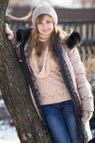Retrato del invierno de una mujer cerca del árbol Imagen de archivo libre de regalías