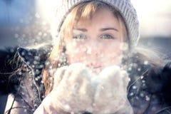 Retrato del invierno de una mujer con nieve en manos Imagen de archivo