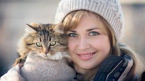 Retrato del invierno de una mujer con un gato Foto de archivo