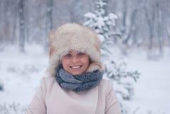 Retrato del invierno de una mujer en la capa blanca durante las nevadas en un parque Foto de archivo
