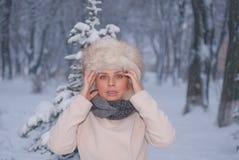 Retrato del invierno de una mujer en la capa blanca durante las nevadas en un parque Fotos de archivo libres de regalías