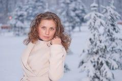 Retrato del invierno de una mujer en la capa blanca durante las nevadas en un parque Imagen de archivo libre de regalías
