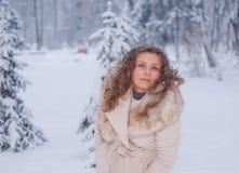 Retrato del invierno de una mujer en la capa blanca durante las nevadas en un parque Fotos de archivo