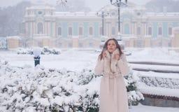 Retrato del invierno de una mujer en la capa blanca durante las nevadas en un parque Imagen de archivo