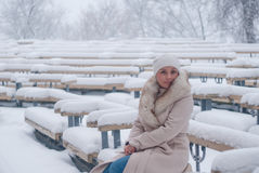Retrato del invierno de una mujer en la capa blanca durante las nevadas en un parque Imagenes de archivo