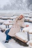 Retrato del invierno de una mujer en la capa blanca durante las nevadas en un parque Foto de archivo libre de regalías