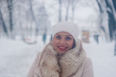 Retrato del invierno de una mujer en la capa blanca durante las nevadas en un parque Imágenes de archivo libres de regalías