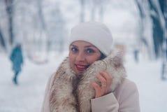 Retrato del invierno de una mujer en la capa y el sombrero blancos durante las nevadas en un parque Foto de archivo