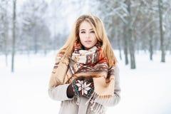 Retrato del invierno de una mujer joven hermosa con la bufanda cerca de nevoso Imágenes de archivo libres de regalías