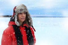 Retrato del invierno de una mujer que lleva un sombrero peludo de la aviación y una chaqueta roja imagenes de archivo