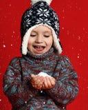 Retrato del invierno del niño pequeño lindo que lleva el estudio acogedor caliente de la ropa tirado con nieve foto de archivo