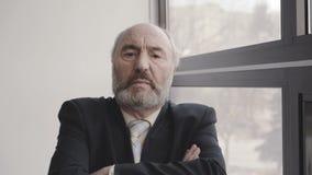 Retrato del jefe mayor con las manos cruzadas y mirada seria 4K almacen de metraje de vídeo