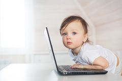 Retrato del juego bastante pequeño del bebé con un ordenador portátil Fotos de archivo