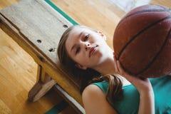 Retrato del jugador de básquet de sexo femenino con la bola que miente en banco ante el tribunal Imágenes de archivo libres de regalías