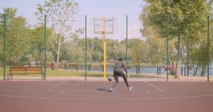 Retrato del jugador de básquet de sexo masculino afroamericano deportivo que lanza una bola en un aire libre del aro en la corte  metrajes