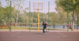 Retrato del jugador de básquet de sexo masculino afroamericano deportivo que lanza una bola en un aro en la corte en la ciudad ur almacen de metraje de vídeo