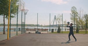 Retrato del jugador de básquet de sexo masculino afroamericano feliz deportivo que lanza una bola en un aro y que celebra con almacen de video