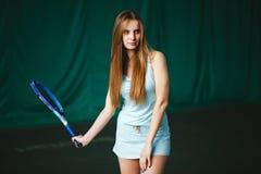 Retrato del jugador de tenis de la chica joven en la acción en un campo de tenis interior Fotografía de archivo libre de regalías