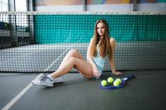 Retrato del jugador de tenis de la chica joven en un campo de tenis interior Fotos de archivo libres de regalías