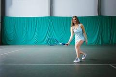 Retrato del jugador de tenis de la chica joven en un campo de tenis interior Foto de archivo libre de regalías