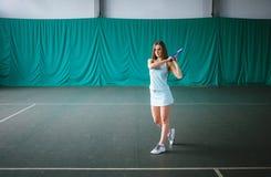 Retrato del jugador de tenis de la chica joven en un campo de tenis interior Imagen de archivo libre de regalías