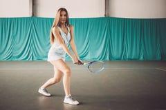 Retrato del jugador de tenis de la chica joven en un campo de tenis interior Fotos de archivo