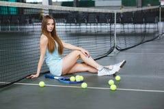 Retrato del jugador de tenis de la chica joven en un campo de tenis interior Foto de archivo