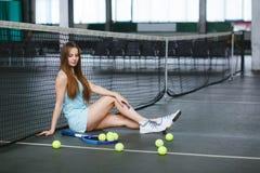 Retrato del jugador de tenis de la chica joven en un campo de tenis interior Imagen de archivo