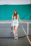Retrato del jugador de tenis de la chica joven en un campo de tenis interior Imagenes de archivo