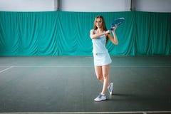 Retrato del jugador de tenis de la chica joven en un campo de tenis interior Fotografía de archivo libre de regalías